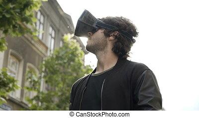 Teenager man using virtual reality headset walking on urban street
