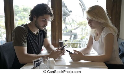 Young couple sitting at cafe table and texting messages on...