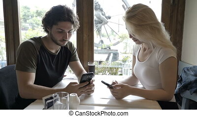 Young beautiful romantic couple sitting in restaurant using...