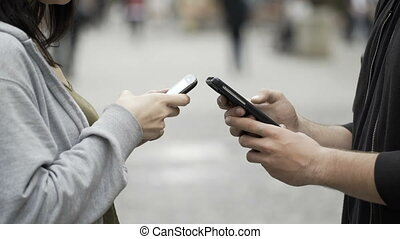 Closeup of two teenagers holding smartphones in public...