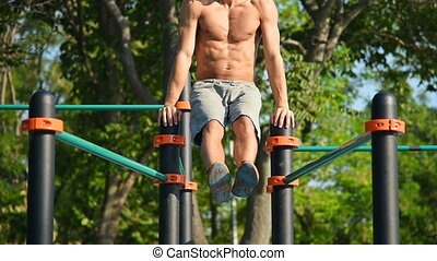 Man Performs A Power Exercise On Uneven Bars - Muscular Man...