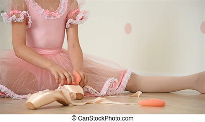 Ballerina Gathers Her Pointe - Ballerina Girl Sitting On...