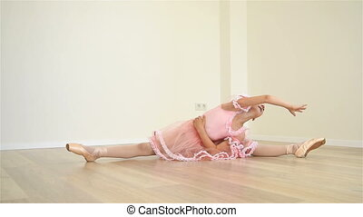 Llittle Ballerina Sitting On Floor In Dance Studio And Does...