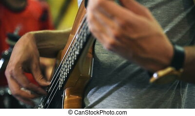 Hands Of Man Playing Electrical Bass Guitar - Close Up Of...