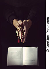 Hands holding rosary and folded in prayer