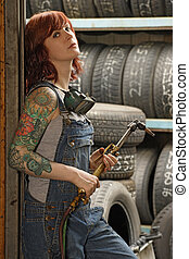 Female welder with tattoos