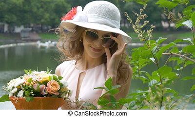Portrait of a beautiful girl in sunglasses and a white hat...