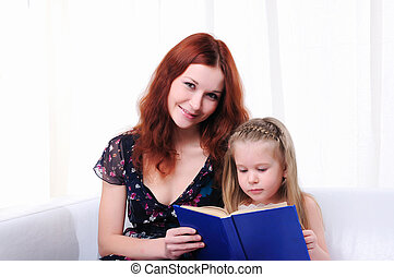 little girl and her mother read a book - The little girl and...