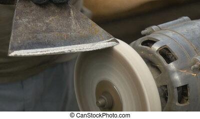 A man sharpens a big ax close-up - A man sharpens a big ax....