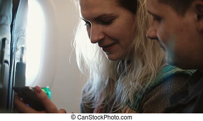 Young beautiful couple traveling by plane. Blonde woman and...
