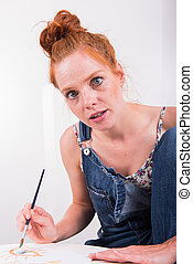 young red-haired woman paints in her spare time