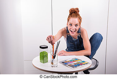 have young red-haired woman paints picture in her spare time