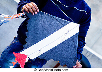 Boy holding a handmade paper kite on the popular festivals...