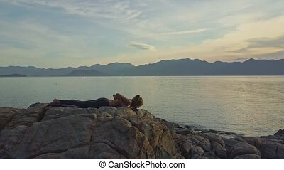 Girl with Ponytail Lies in Yoga Pose on Stone at Sunrise