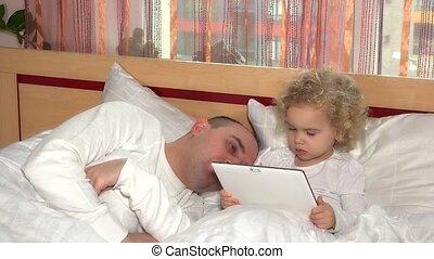 Sweet toddler girl using tablet computer wake up sleeping...