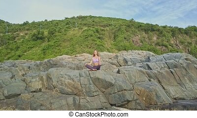 Drone Moves to Girl Sitting in Yoga Pose on High Rock -...