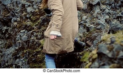 Young tourist woman holding camera and hiking in the mountains near the river. Girl exploring the sights alone.