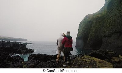 Back view of young traveling couple standing on the rocks near the sea and enjoying the beautiful view together.