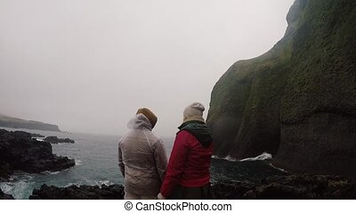 Back view of young tourists couple in raincoats standing on...