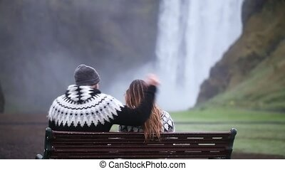 Back view of young couple sitting on the bench and resting. Beautiful landscape of the Skogafoss waterfall in Iceland.