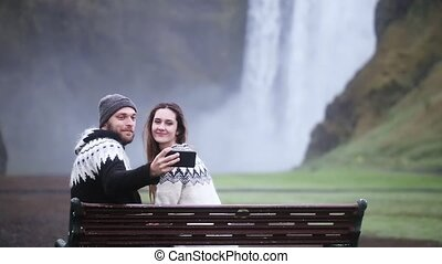 Young happy couple sitting on the bench and taking photo on smartphone near the Skogafoss waterfall in Iceland.