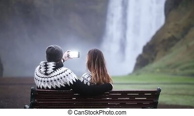 Young couple taking the photo on smartphone of the beautiful waterfall Skogafoss in Iceland, famous tourist place.