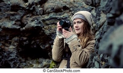 Young beautiful woman holding camera and taking photos in...