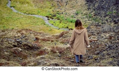 Back view of young traveling woman walks in mountain valley near river alone. Female exploring new place and thinking.