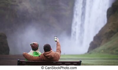 Back view of young couple sitting on the bench and taking selfie photo on smartphone. Skogafoss waterfall in Iceland.