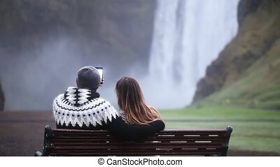Back view of young couple sitting on bench and taking selfie photo on smartphone near the Skogafoss waterfall in Iceland