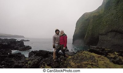Young traveling couple in raincoats standing on the shore of...