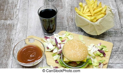 Home made hamburger with fries on wooden table. Fast food...