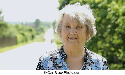 Portrait of smiling elderly woman aged 80s in park -...