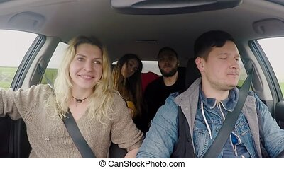 Two young happy couple traveling by car together. Friends...