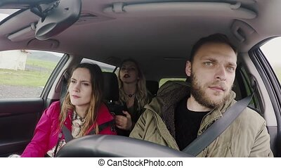 Young happy people traveling by car together. Friends trying to find the way, man driving the vehicle.