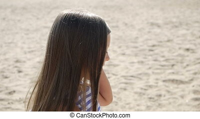 girl in a striped dress and long hair goes on back