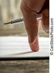 Male hand pointing to a line at the end of a document