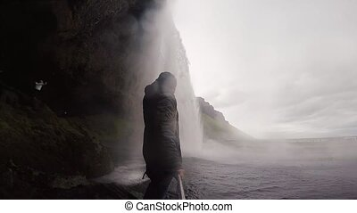Young tourist man holding selfie stick and shooting on gopro camera powerful waterfall Seljalandsfoss in Iceland.