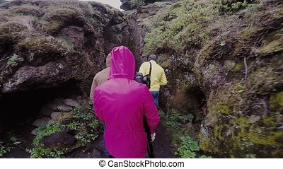 Back view of friends walking in mountains in rainy day. Group of people hiking together, spending leisure time on nature