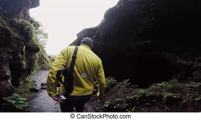 Back view of man in raincoat walking in mountains in rainy...