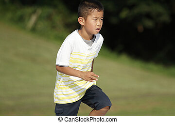 Japanese boy running on the grass (second grade at elementary school)