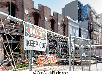 Danger Keep Out sign in front of a falling-down, dilapiated building