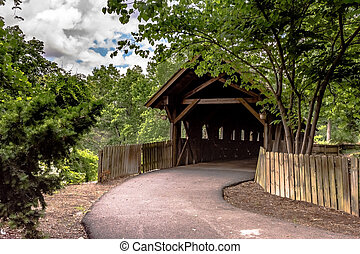 Path to a covered bridge - Paved pathway leading to a...