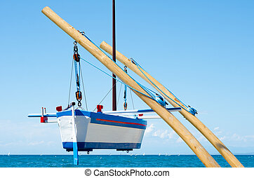 hanging boat over the sea