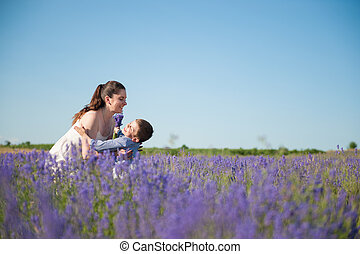 happy child falling into the arms of smiling mother on the...