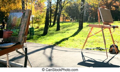 painting autumn landscape - hand of the artist drawing an...