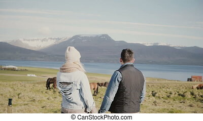 Back view of young tourists couple standing on the Iceland...