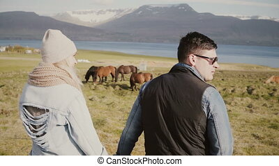 Back view of young couple on the Iceland farm and looking on the horses. Man and woman spending time on the nature.