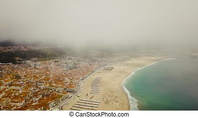 View on Nazare atlantic coast and sandy beach in Portugal. Flight on a drone in the clouds