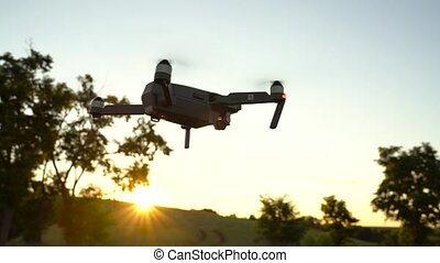 Small quadrocopter flying against the sky. Slow motion -...